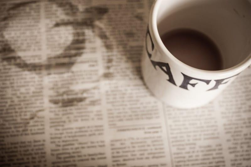 Abandoned Coffee Mug on a Coffee-Stained Newspaper