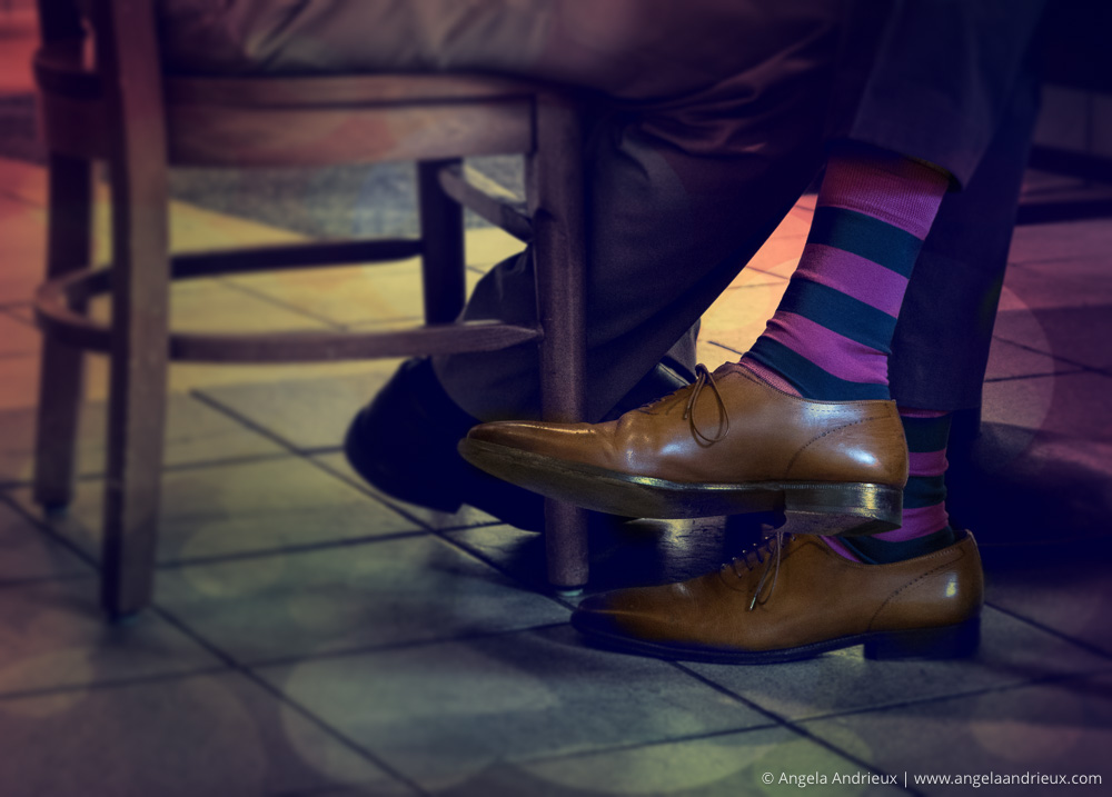 Man at cafe table, seated with purple striped socks and brown shoes | Topaz Texture Effects