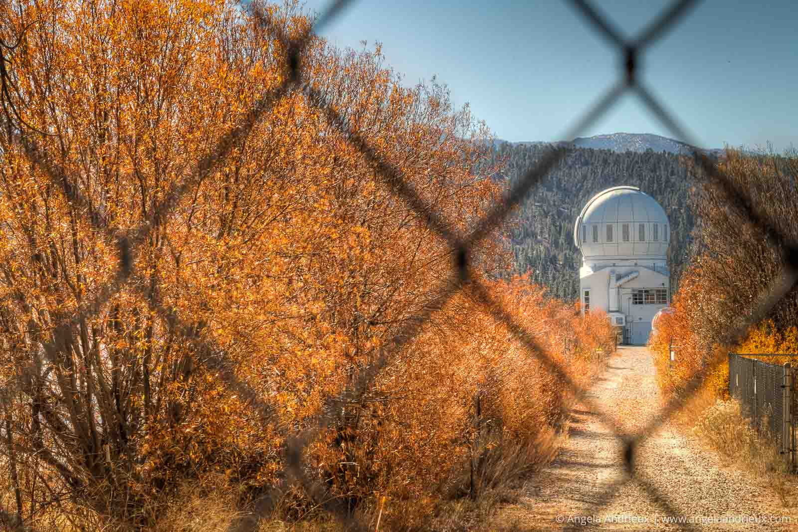 A glimpse of the Big Bear Solar Observatory through a chain link fence, surrounded by fall colors