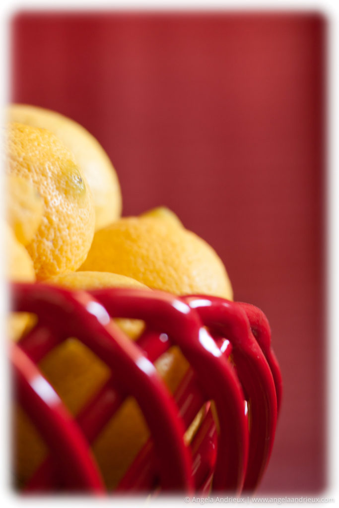 Lemons in a red bowl with a red background