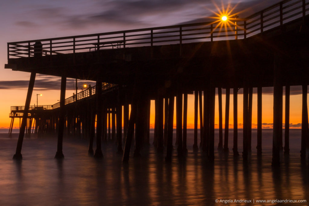 Pismo Beach Pier silhouetted against the sunset with a starburst from a streetlight through the rails