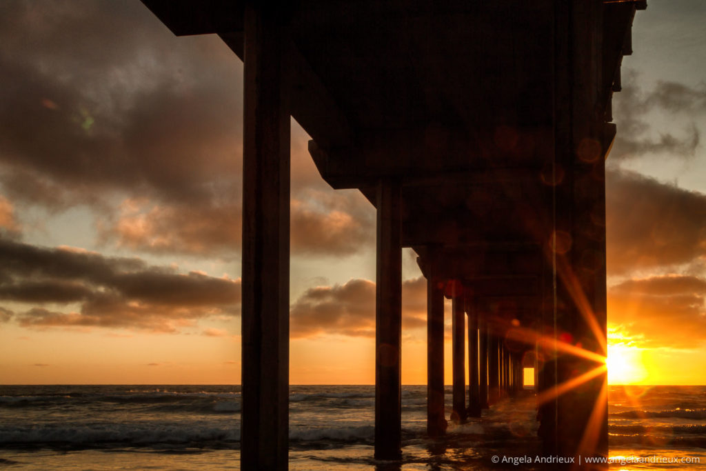 Scripps Pier in La Jolla with sunset sunburst and spots on my lens from sea spray