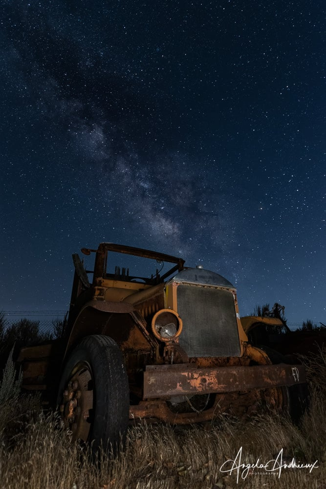 Old rusty truck at night with the Milky Way in the sky