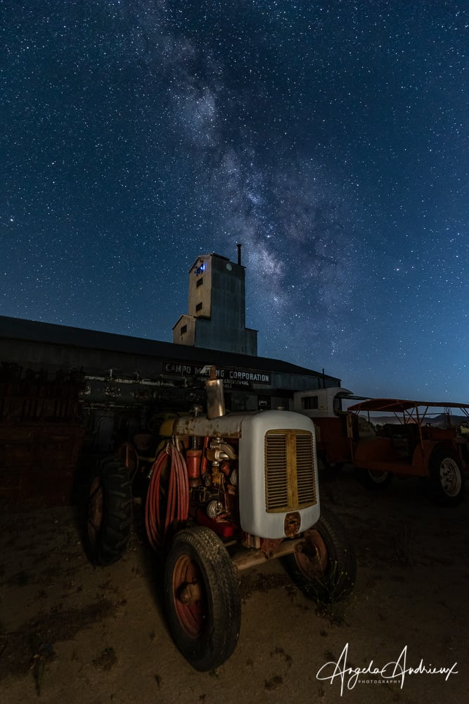 Old rusty tractor at night with the Milky Way in the sky and the Campo Motor Transport Museum in the background