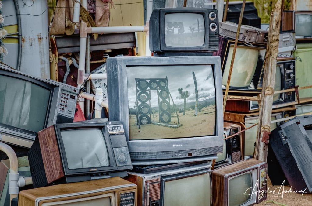 Stack of discarded television sets with reflections of desert scenes
